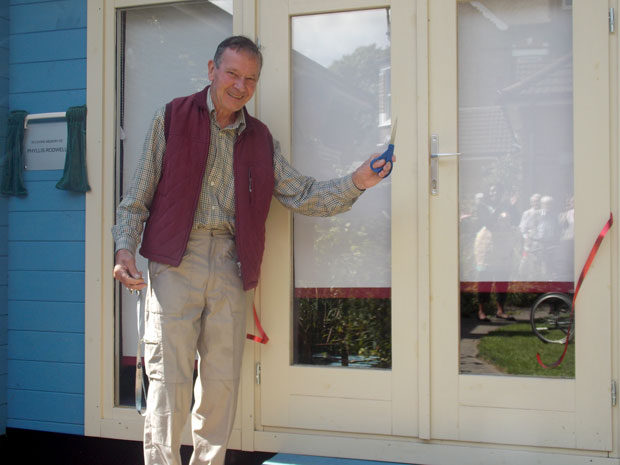 Keith Rodwell cuts opening ribbon for the Reminiscence Cabin at MindCare Dementia Support
