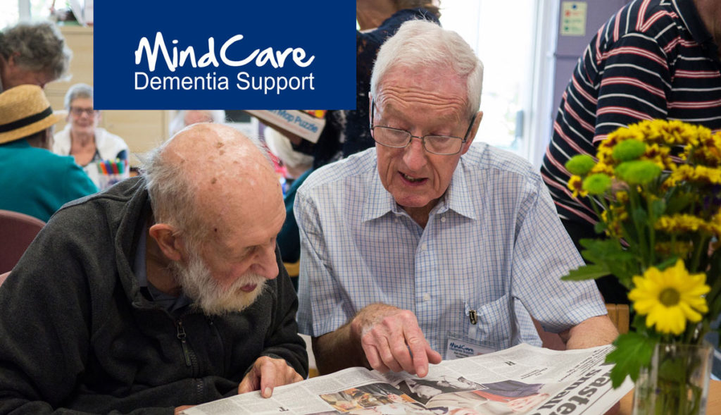 Male dementia Support Worker reading newspaper with man with dementia