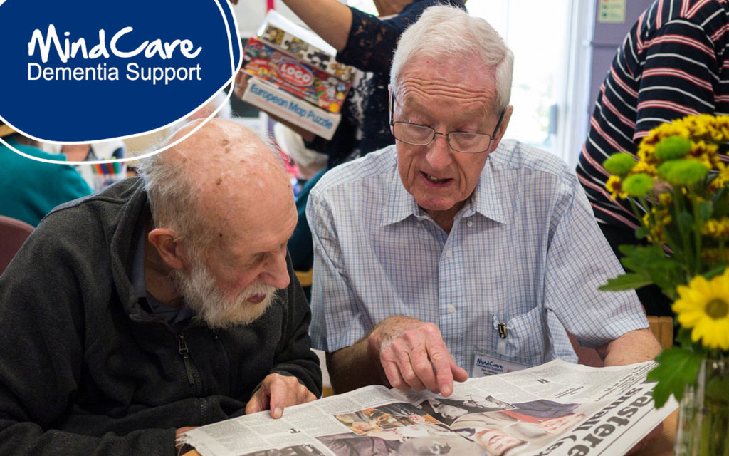 Dementia Support Worker reading newspaper with man with dementia