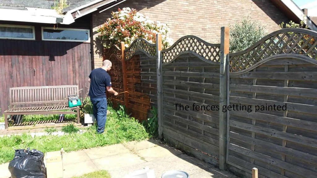 VINCI volunteer painting the garden fences at Orpington MindCare Dementia Support