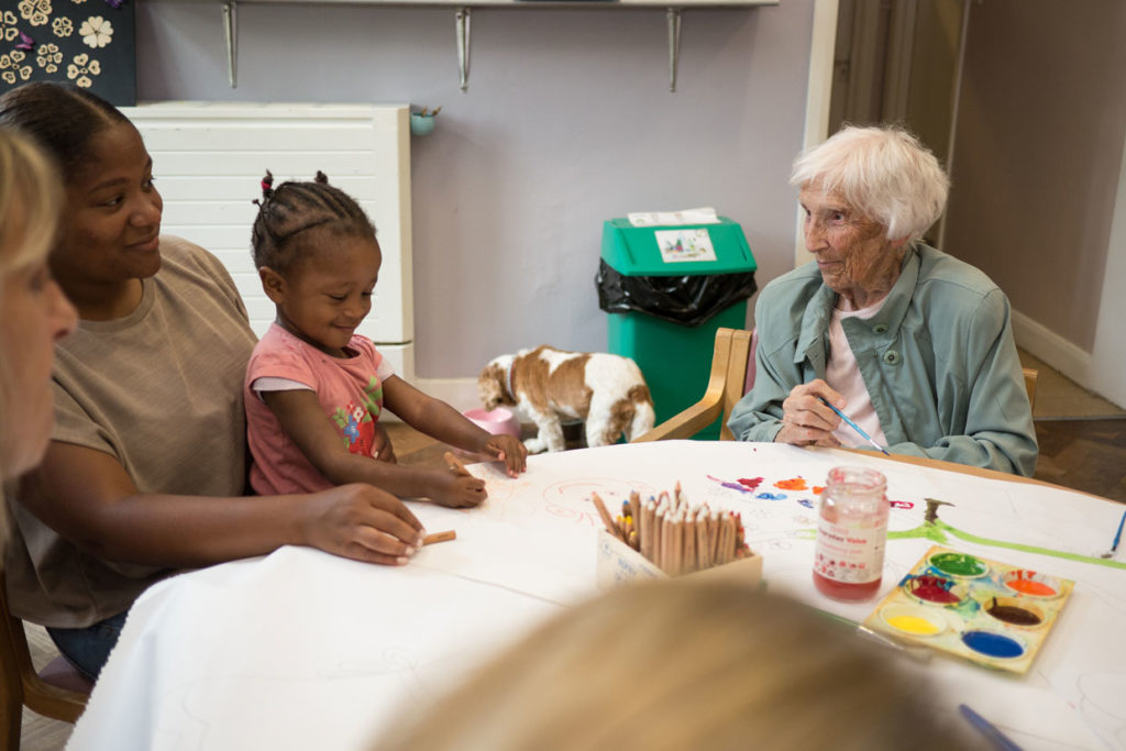 Mother and toddler in arts activity with people with dementia