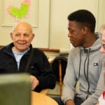 Man with dementia talking to a young male volunteer