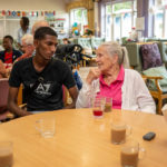 young man talking to an older lady at dementia centre