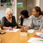 Women with dementia doing art with care manager and young volunteer