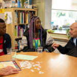 young volunteers talking with an older man with dementia