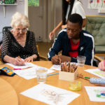 women with dementia and young male volunteer doing artwork