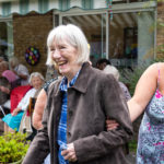 Person with dementia with family carer enjoying the garden party
