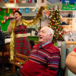 Man sitting and enjoying live singing at MindCare Dementia Support Christmas Party